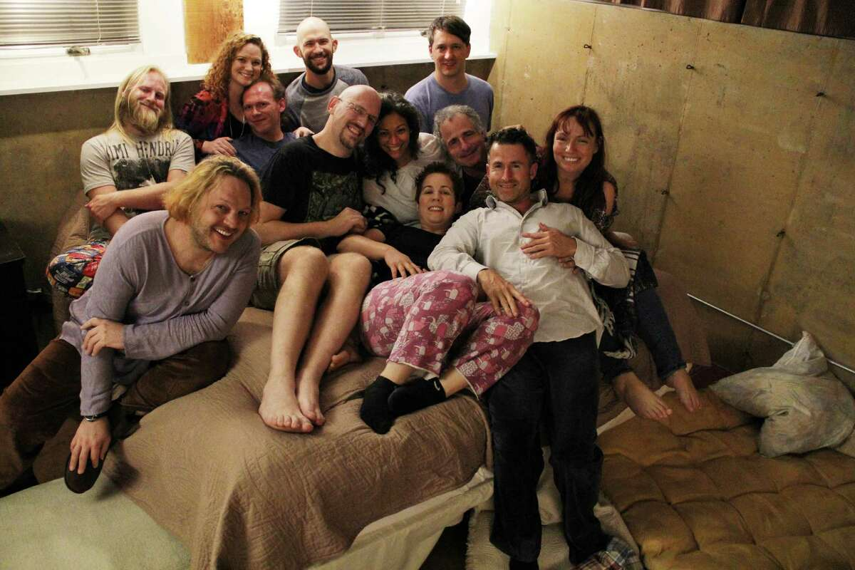 A dozen people clad in pajamas squeeze in for one last snuggle after a three-hour cuddle party in Austin on Nov. 17, 2016.