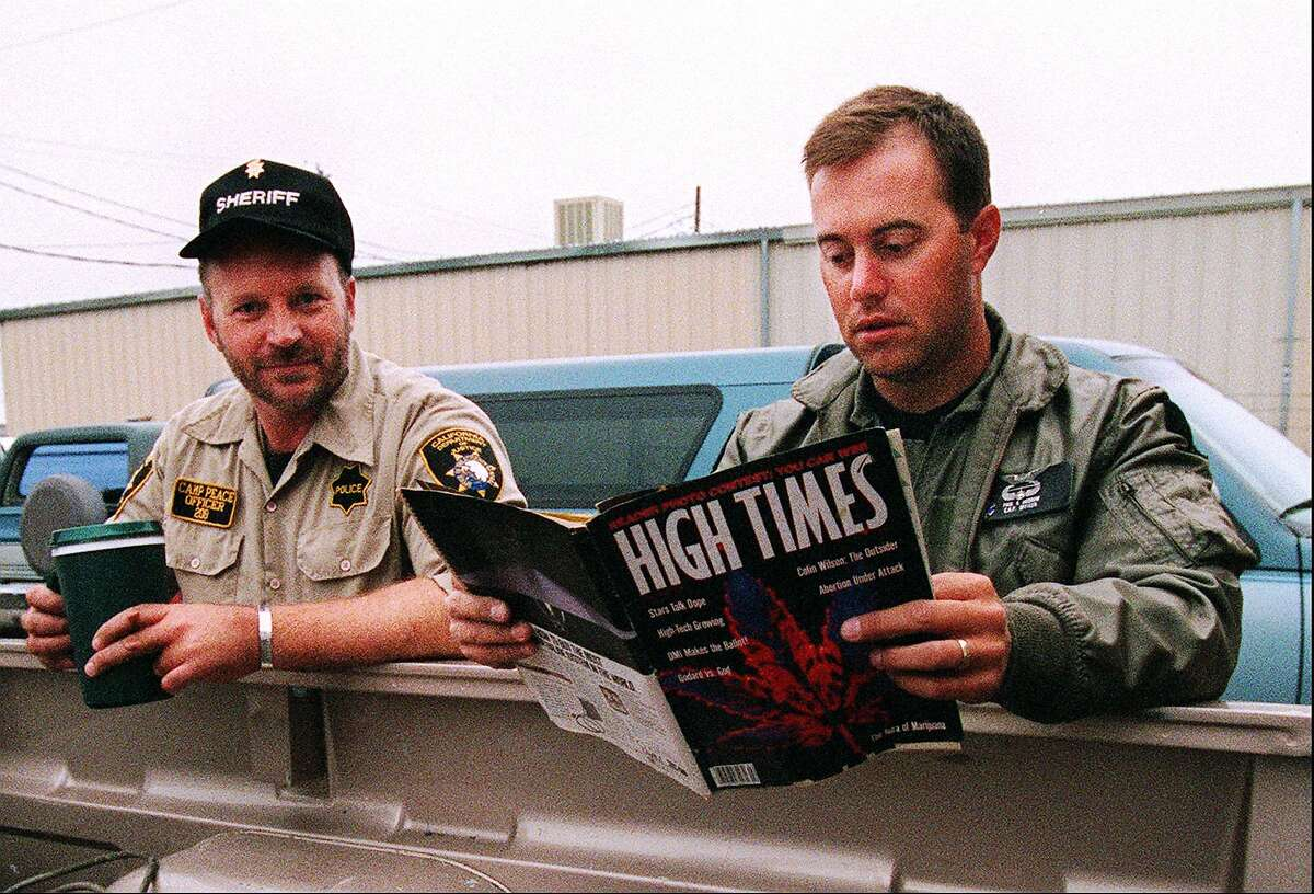 Law enforcement officer Paul Budrow, right, reads a copy of High Times magazine, as officer Wray Graham looks on, while waiting to be deployed to a marijuana patch near Ukiah, Calif., Tuesday Sept. 22, 1998. They read the magazine to keep up on the drug culture. Officers come from across the state to spend eight weeks with the multi-agency task force called CAMP - the Campaign Against Marijuana Planting. In camouflage, they swoop onto hillsides from helicopters and use machetes to hack down hundreds of marijuana plants. (AP Photo/George Nikitin)
