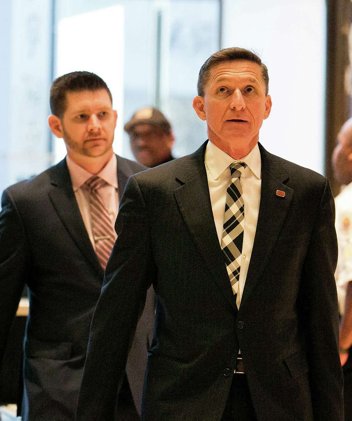 Retired Army Lt. Gen. Michael Flynn, foreground, whom President-elect Donald Trump tapped to be his national security advisor, arrives at Trump Tower in New York for meetings on Nov. 17, 2016. Flynn is followed by his son, Michael Flynn Jr. (Sam Hodgson/The New York Times)