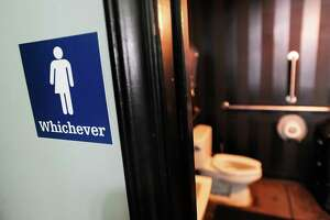 A gender neutral sign is posted outside a bathroom at Oval Park Grill on May 11, 2016 in Durham, N.C. (Photo by Sara D. Davis/Getty Images)