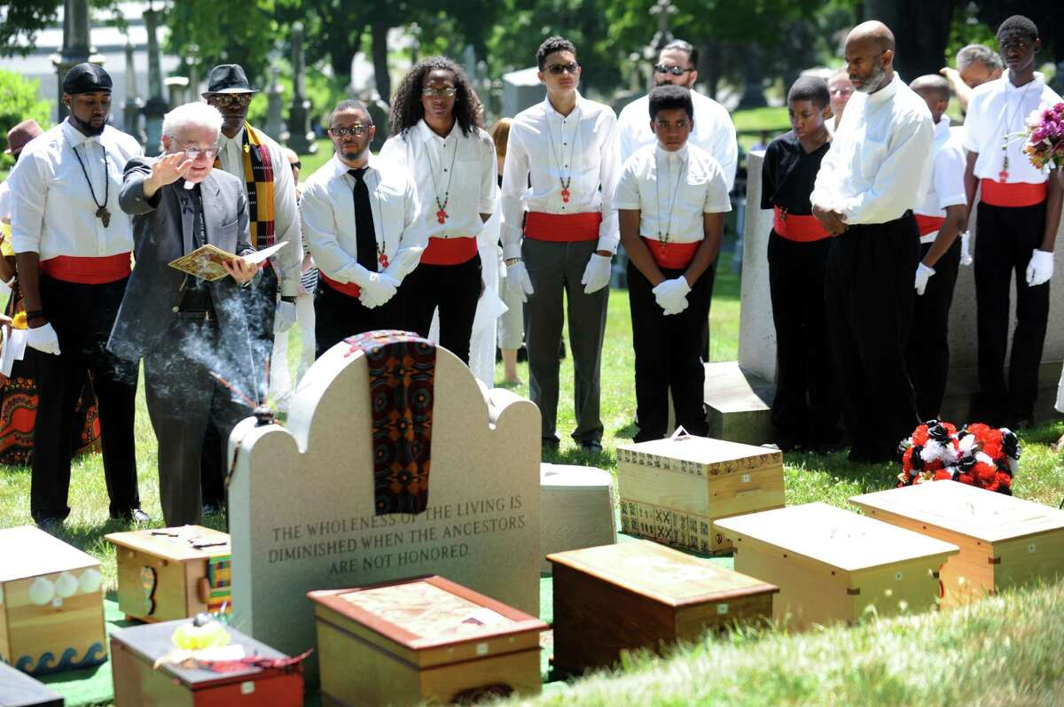 Father James Kane of the Committee for Ecumenical and Interreligious Affairs, second from left, blesses the headstone during the service of 14 people enslaved in life as part of the Schuyler Flatts Burial Ground Project on Saturday, June 18, 2016, at St. Agnes Cemetery in Menands, N.Y. (Cindy Schultz / Times Union)
