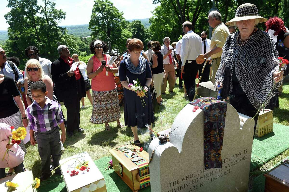 Mayor Kathy Sheehan, center, joins others in placing flowers on the ossuaries of 14 people enslaved in life as part of the Schuyler Flatts Burial Ground Project service on Saturday, June 18, 2016, at St. Agnes Cemetery in Menands, N.Y. (Cindy Schultz / Times Union)