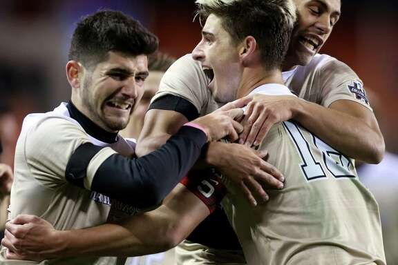 Wake Forest Ian Harkes (16) celebrates with teammates after scoring the game-winning goal during the second overtime against University of Denver at the 2016 NCAA soccer Men's College Cup semifinal game at BBVA Compass Stadium Friday, Dec. 9, 2016, in Houston. Harkes scored with an assist from Jon Bakero (7), left, who also made a goal during the first half of the game. The Demon Deacons beat the Pioneers 2-1.