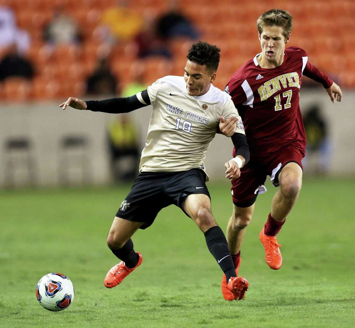Denver's Karsten Hanlin (17) tries to stop Wake Forest's Alex Knox (18) from getting control of the ball during the first half of the NCAA soccer men's College Cup semifinal Friday, Dec. 9, 2016, in Houston. (Yi-Chin Lee/Houston Chronicle via AP )