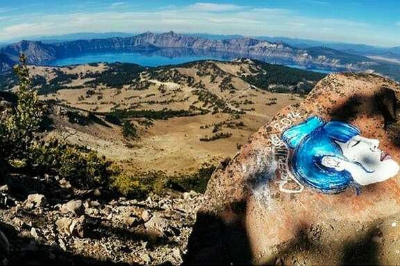 FILE - This undated file photo taken from an Instagram posting shows an overlook of Crater Lake in Oregon with a rock painting. As investigators find more of the eerie faces scrawled on rocks in some of the West�s most picturesque landscapes, park managers are trying to figure out how they�ll get rid of the graffiti-like paintings. Casey Nocket, the 21-year-old suspect identified by the park service this week, allegedly used acrylic paint and markers to leave eerie faces in at least eight parks across California, Colorado, Utah and Oregon, including the one in this photo. (AP Photo/Instagram, File)