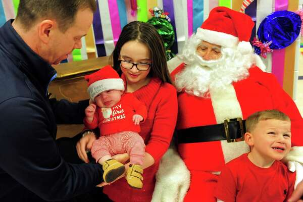 Steve Kutzscher, of Oxford, hands his 3 month old son Ashton to his daughter Alexa, 11, as she and her little brother Austin, 4, pose for a photo with Santa during The Oxford Festival of Trees at Oxford High School in Oxford, Conn. on Friday Dec. 9, 2016. The festival continues on Saturday starting at 4 p.m. with face painting, another visit by Santa and a pizza party with him and much more.