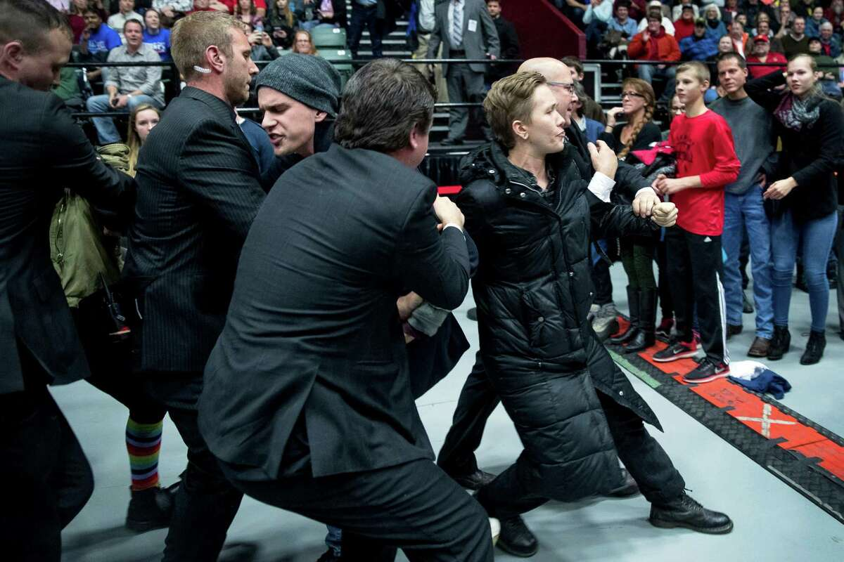 People are removed for disrupting President-elect Donald Trump as he speaks at a rally at DeltaPlex Arena, Friday, Dec. 9, 2016, in Grand Rapids, Mich. (AP Photo/Andrew Harnik)