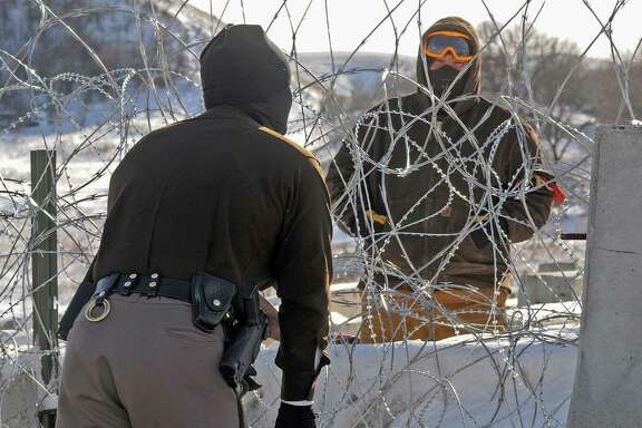 A law enforcement officer speaks to a protester against the Dakota Access Pipeline through a wall of razor wire on the Backwater Bridge over Cantapeta Creek on Thursday afternoon, Dec. 8, 2016. Protesters have been trespassing at the site and cutting wire in attempts to gain access to the pipeline work area in southern Morton County. (Tom Stromme/The Bismarck Tribune via AP)