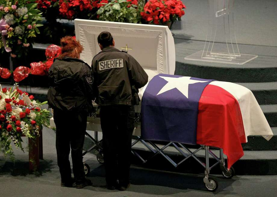 Bexar County Sheriff's Office Deputies Margie Miranda (left) and Thelma Castillo pause at the casket of BCSO Deputy Dora Linda Solis Nishihara during the public viewing held Friday Dec. 9, 2016 at Sendero Assembly of God Church. Nishihara died after driving her vehicle into a large sinkhole Sunday evening on the Southwest Side. Photo: Edward A. Ornelas /San Antonio Express-News / © 2016 San Antonio Express-News
