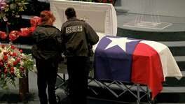 Bexar County Sheriff's Office Deputies Margie Miranda (left) and Thelma Castillo pause at the casket of BCSO Deputy Dora Linda Solis Nishihara during the public viewing held Friday Dec. 9, 2016 at Sendero Assembly of God Church. Nishihara died after driving her vehicle into a large sinkhole Sunday evening on the Southwest Side.