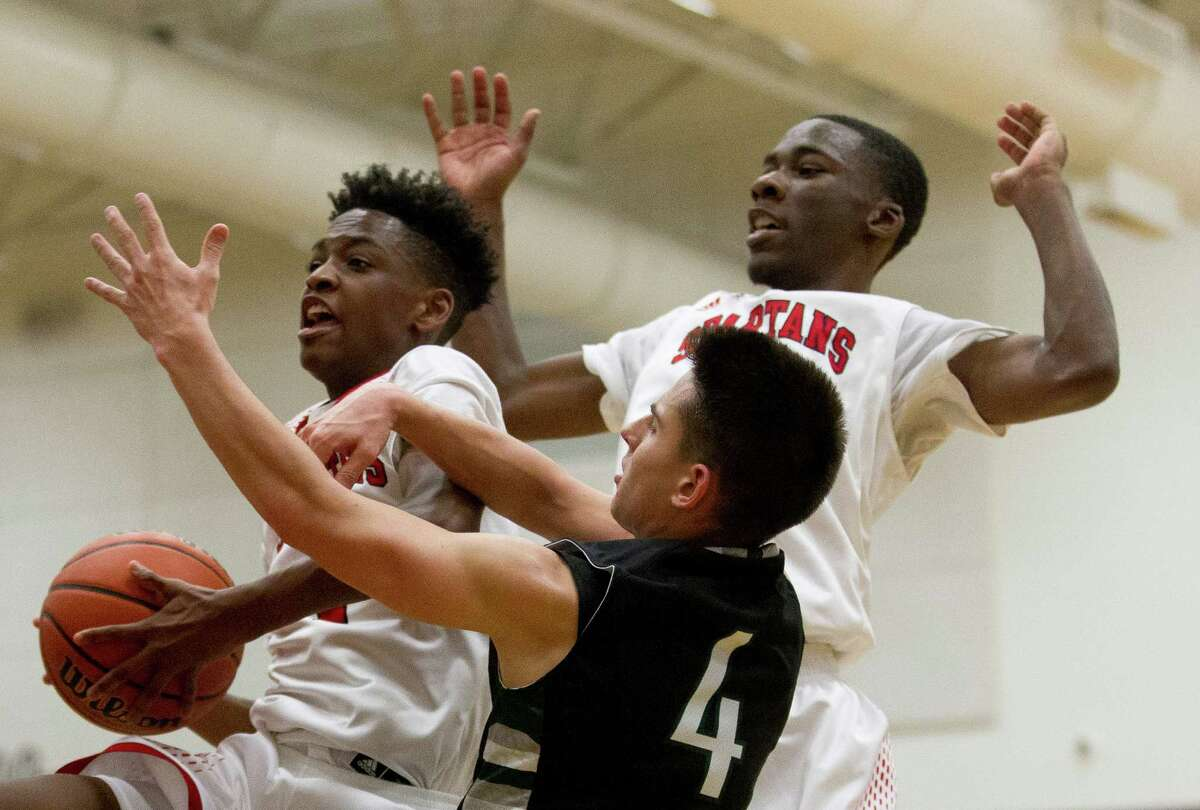 Porter guard Jeremiah Palmer (4) grabs a rebound over Kingwood Park Colton Killian (4) and Porter teammate Trevor Jones (41) during the fourth quarter of a District 21-5A boys high school basketball game at Porter High School Friday, Dec. 9, 2016, in Porter. Kingwood Park defeated Porter 62-49.