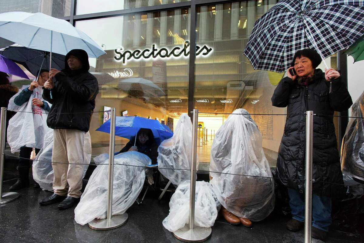 Customers cover up under umbrellas in New York last month as they wait to purchase Spectacles, the $130 sunglasses that take video for sharing on Snapchat. You can't just order one online - yet.