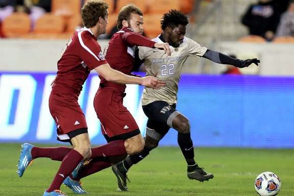 Denver players try to stop Wake Forest's Ema Twumasi (22) advancing toward the goal during the first half  of the NCAA soccer men's College Cup semifinal Friday, Dec. 9, 2016, in Houston. (Yi-Chin Lee/Houston Chronicle via AP )