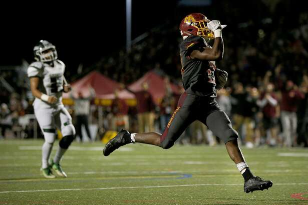 Menlo-Atherton Bears running back Jordan Mims (23) runs in the end zone for a touchdown as Manteca Buffaloes linebacker Devyn Gonzales (31) watches him score on Friday, Dec. 9, 2016 in Atherton, Calif. The CIF Regional NorCal Division 3-AA football game was played between Menlo-Atherton High School and Manteca High School. At half time, Menlo-Atherton leads 21-7.
