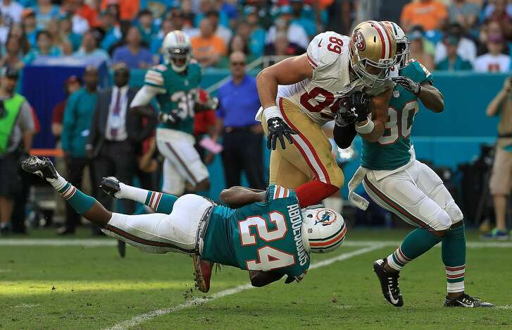 MIAMI GARDENS, FL - NOVEMBER 27: Vance McDonald #89 of the San Francisco 49ers is tackled by Isa Abdul-Quddus #24 of the Miami Dolphins during a game  on November 27, 2016 in Miami Gardens, Florida.  (Photo by Mike Ehrmann/Getty Images)