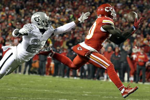 Kansas City Chiefs wide receiver Tyreek Hill (10) makes a touchdown catch in front of Oakland Raiders cornerback David Amerson (29) during the first half of an NFL football game in Kansas City, Mo., Thursday, Dec. 8, 2016. (AP Photo/Charlie Riedel)