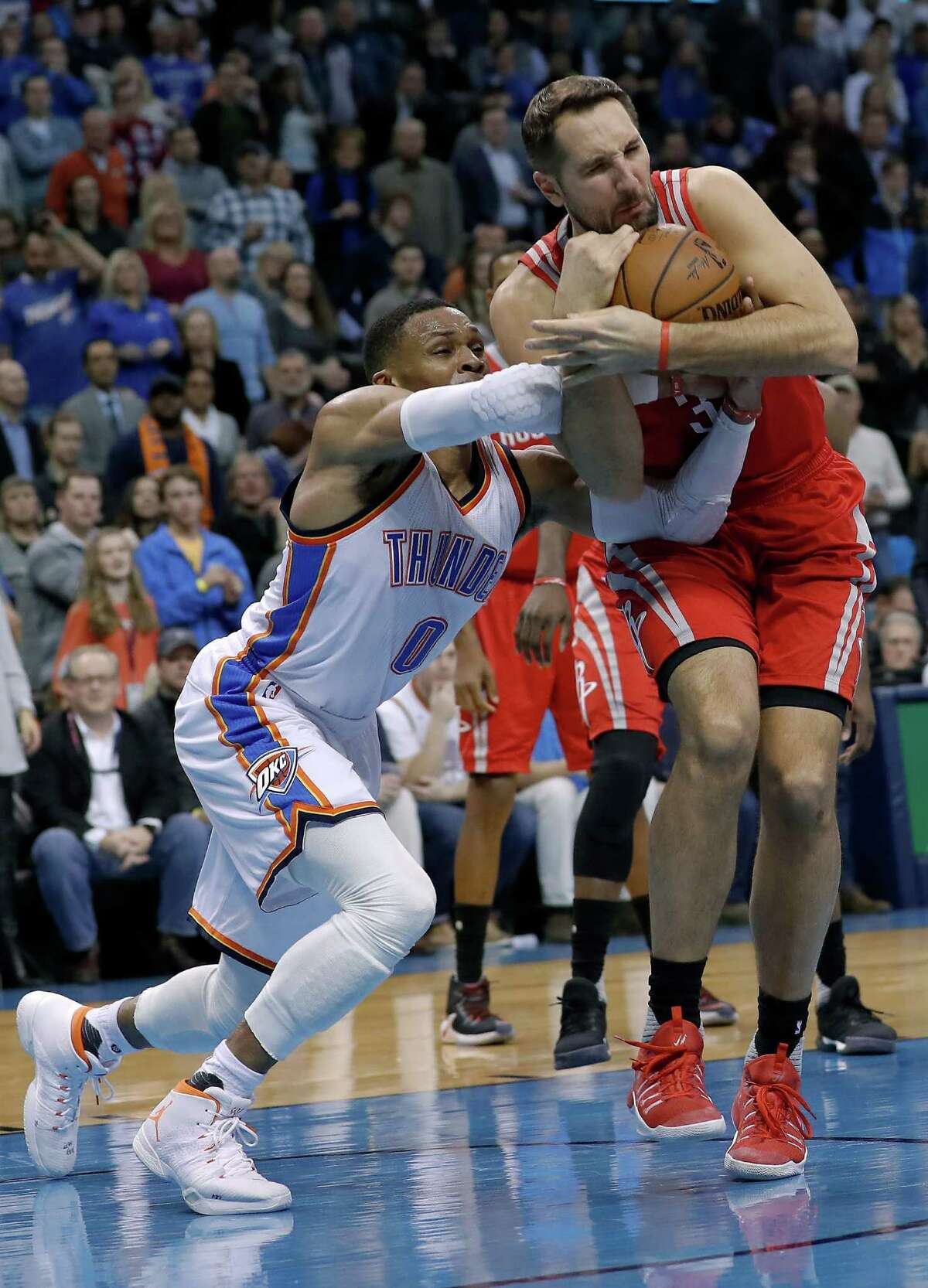 Oklahoma City Thunder guard Russell Westbrook, left, and Houston Rockets forward Ryan Anderson, right, tussle for a loose ball during the second half of an NBA basketball game in Oklahoma City, Friday, Dec. 9, 2016. Houston won 102-99. (AP Photo/Alonzo Adams)