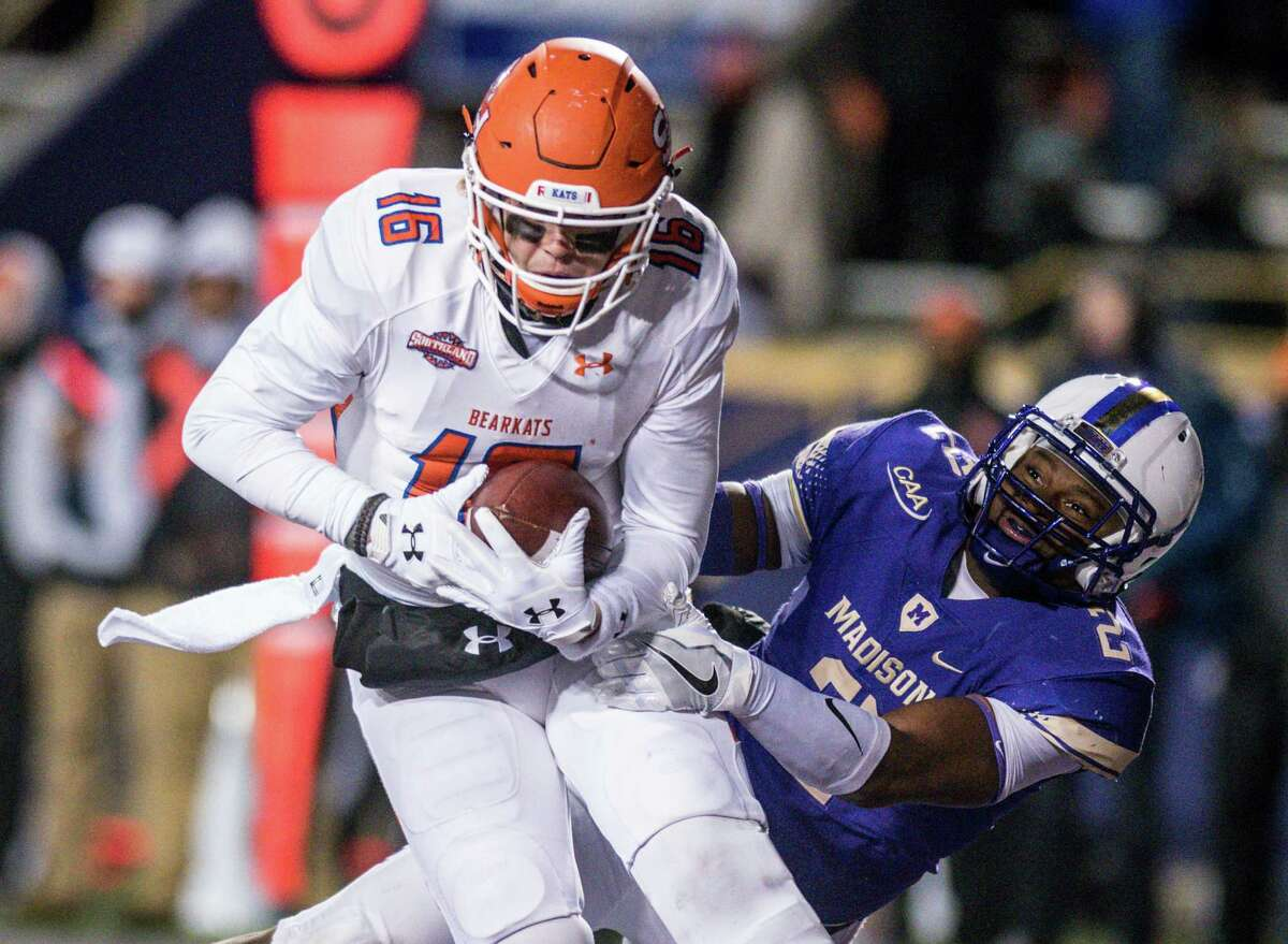 Sam Houston State quarterback Jeremiah Briscoe (16) rolls out of the pocket as James Madison linebacker Dimitri Holloway (2) misses a tackle during the second half of an NCAA college football game in Harrisonburg, Va., Friday, Dec. 9, 2016. (Daniel Lin/Daily News-Record via AP)