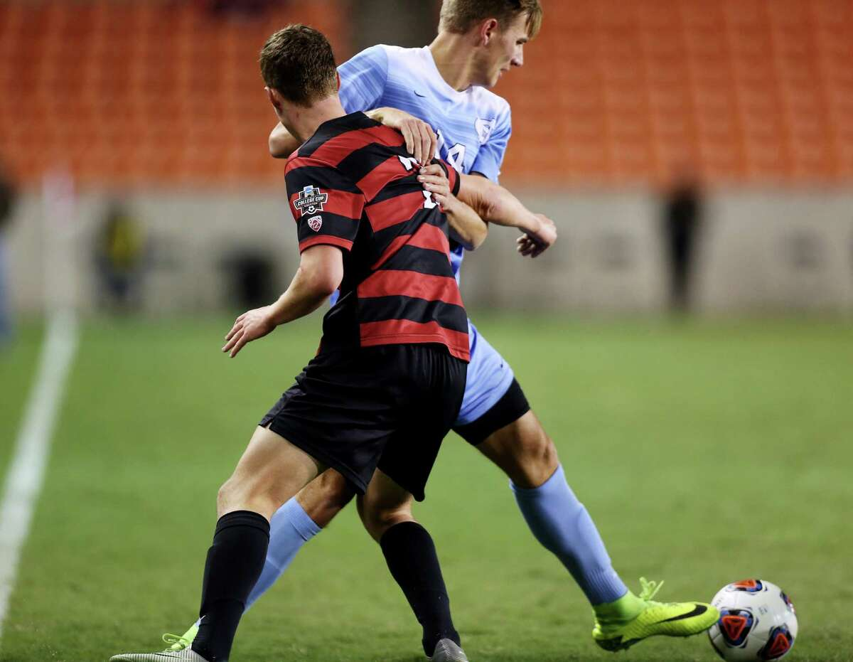 Stanford Tanner Beason (3) and North Carolina Nils Bruening (14) in a locked in position while competing for control of the ball during the second half of the 2016 NCAA soccer Men's College Cup semifinal game at BBVA Compass Stadium Friday, Dec. 9, 2016, in Houston. Stanford beat UNC 10-9 at PK.