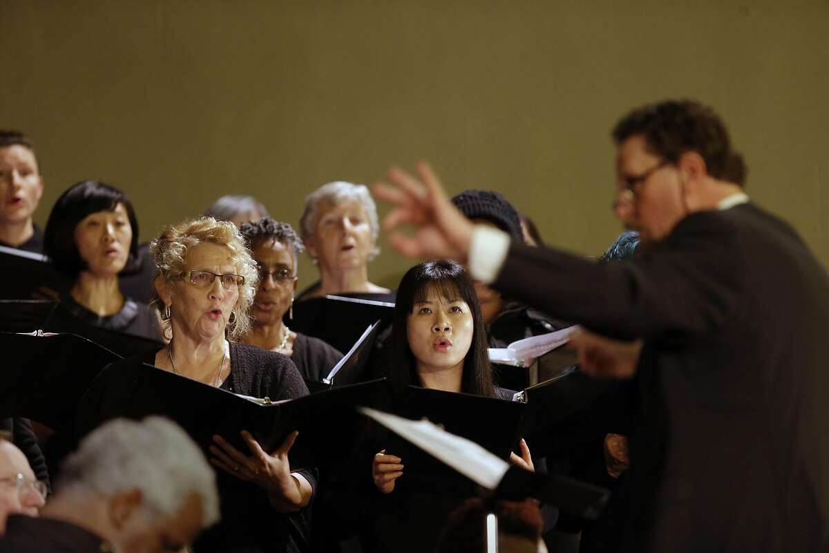 """John Reager directs the chorus during the performance as Laney College's Oakland City Chorus holds """" A Time for Reflection"""" at the First Presbyterian Church in Oakland, California, on Friday December 9, 2016. The benefit was held for chorus member Denalda Siegrist and other victims who perished in the Ghost Ship warehouse fire."""