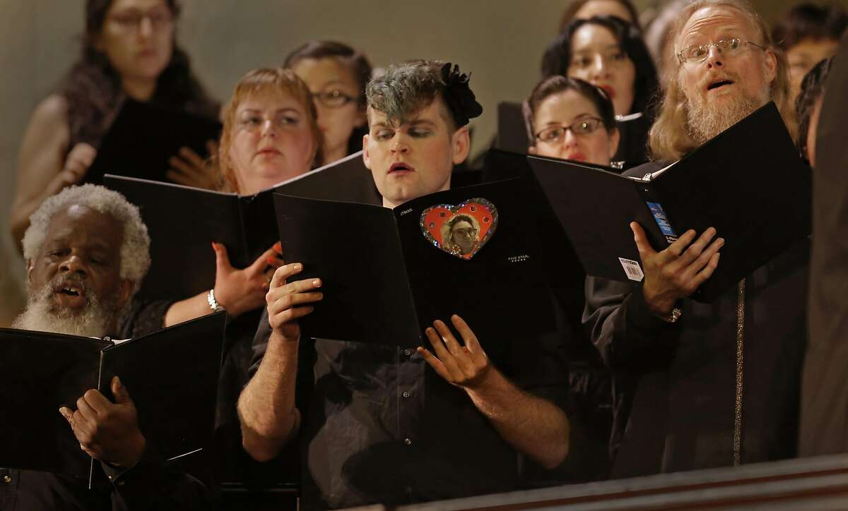 """Tenor, Yacob McCann holds his song book containing a photo of his friend and fellow chorus member Denalda Siegrist during the performance as Laney College's Oakland City Chorus holds """" A Time for Reflection"""" at the First Presbyterian Church in Oakland, California, on Friday December 9, 2016. The benefit was held for chorus member Denalda Siegrist and other victims who perished in the Ghost Ship warehouse fire."""