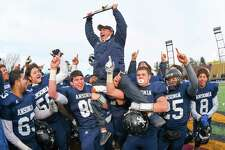 Head Coach Thomas Brockett of the Ansonia Chargers raises the Class S State Championship Trophy after a victory against the Rocky Hill Terriers on December 10, 2016 in New Britain, Connecticut.