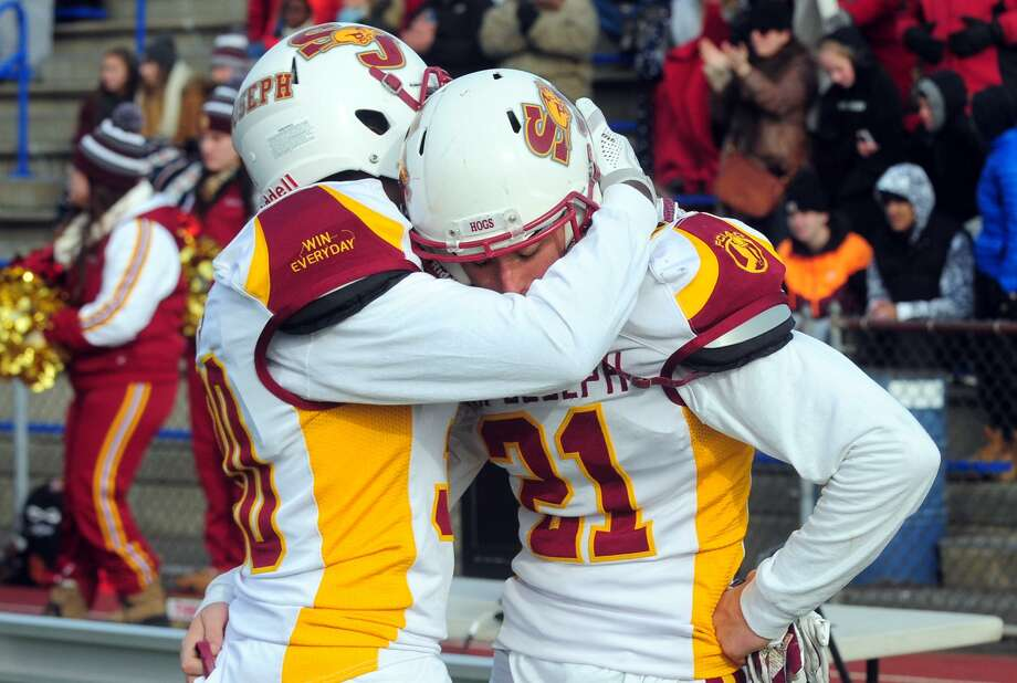 St. Joseph's Josh Menard, left, embraces teammate Mike Dilorio on the sidelines after being defeated by Hillhouse Saturday. Photo: Christian Abraham / Hearst Connecticut Media / Connecticut Post