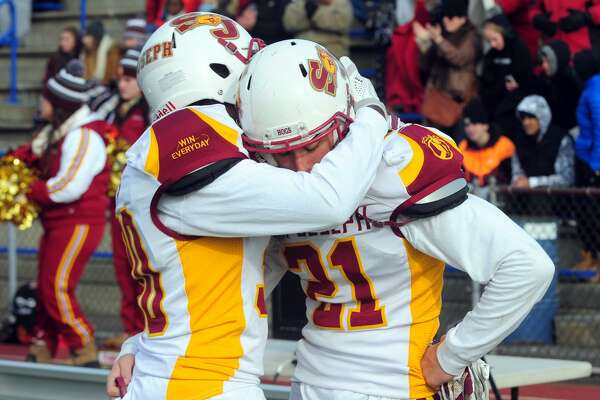 St. Joseph's Josh Menard, left, embraces teammate Mike Dilorio on the sidelines after the team was defeated by Hillhouse during Class M Championship football action in West Haven, Conn. on Saturday Dec. 10, 2016. Final score: 42-21.