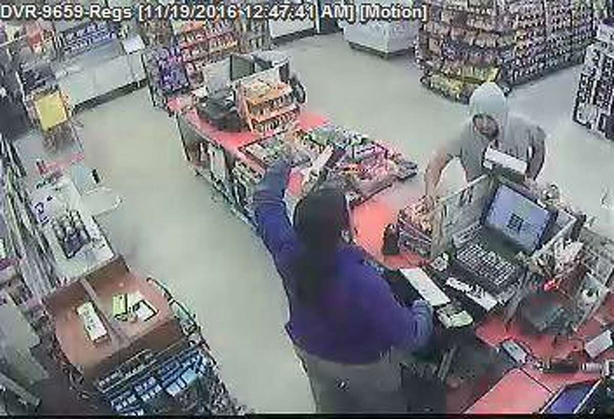 Authorities are looking for the man in a gray hooded sweater. In this photo, Laredo police said he is reaching over the counter for money.