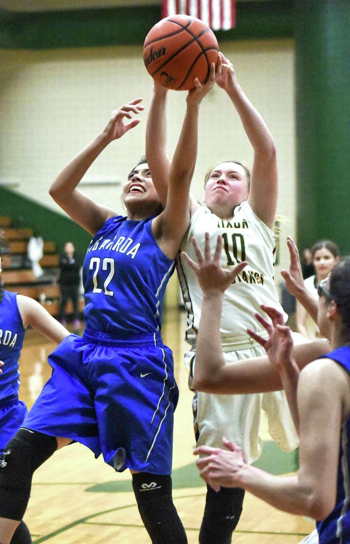 Cigarroa High School Larissa Palomares and Nixon High School Alejandra Gutierrez fight for the rebound on Friday night during a game at Nixon High School.