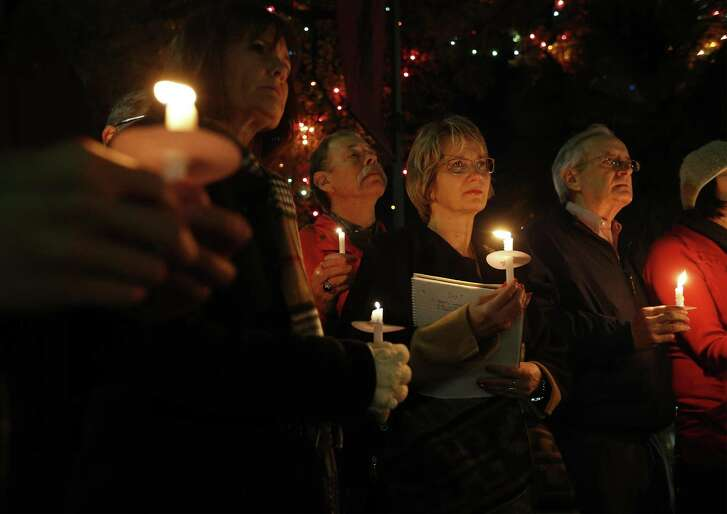 Valerie Redus (third from right) and her husband, Mickey (fourth from right), join others in a candlelight vigil to mark the three-year anniversary of the death of their son, Cameron, in front of the University of the Incarnate Word on Tuesday, Dec. 6, 2016. Cameron was a student at UIW who was shot five times by a campus police officer in 2013. The vigil was held the night before the Redus family attorney goes before State Supreme Court with arguments in the wrongful death suit filed by the Redus family. About 40 people gathered for the vigil - many who were Cameron's classmates.  (Kin Man Hui/San Antonio Express-News)