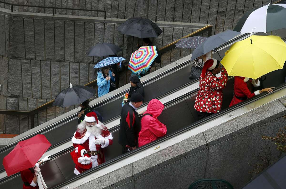 A Santa lookalike rides the escalator at Hallidie Plaza on his way to Union Square for the annual Santacon romp in San Francisco, Calif. on Saturday, Dec. 10, 2016.