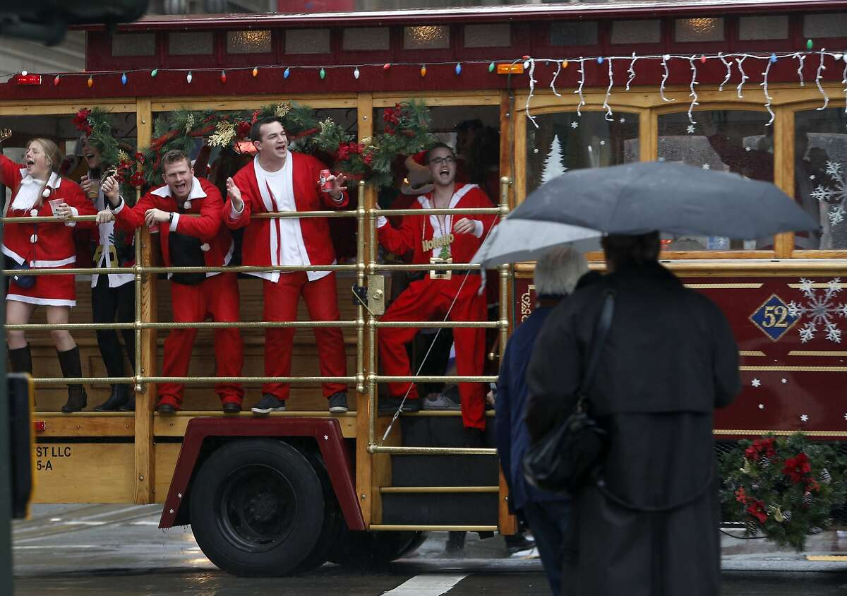 Partiers whoop it up aboard a motorized cable car circling Union Square for the annual Santacon romp in San Francisco, Calif. on Saturday, Dec. 10, 2016.