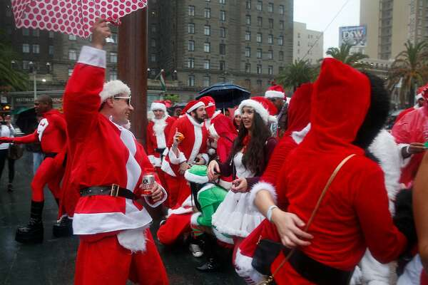 Kris Kringle wannabes scatter to buses for pub crawls in North Beach and the Marina after a group photo on Union Square for the annual Santacon romp in San Francisco, Calif. on Saturday, Dec. 10, 2016.