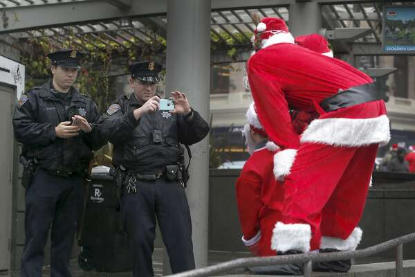Police officers John Siracusa (left) and John Quinlan snap photos for Kris Kringle wannabes attending the annual Santacon romp at Union Square in San Francisco, Calif. on Saturday, Dec. 10, 2016.