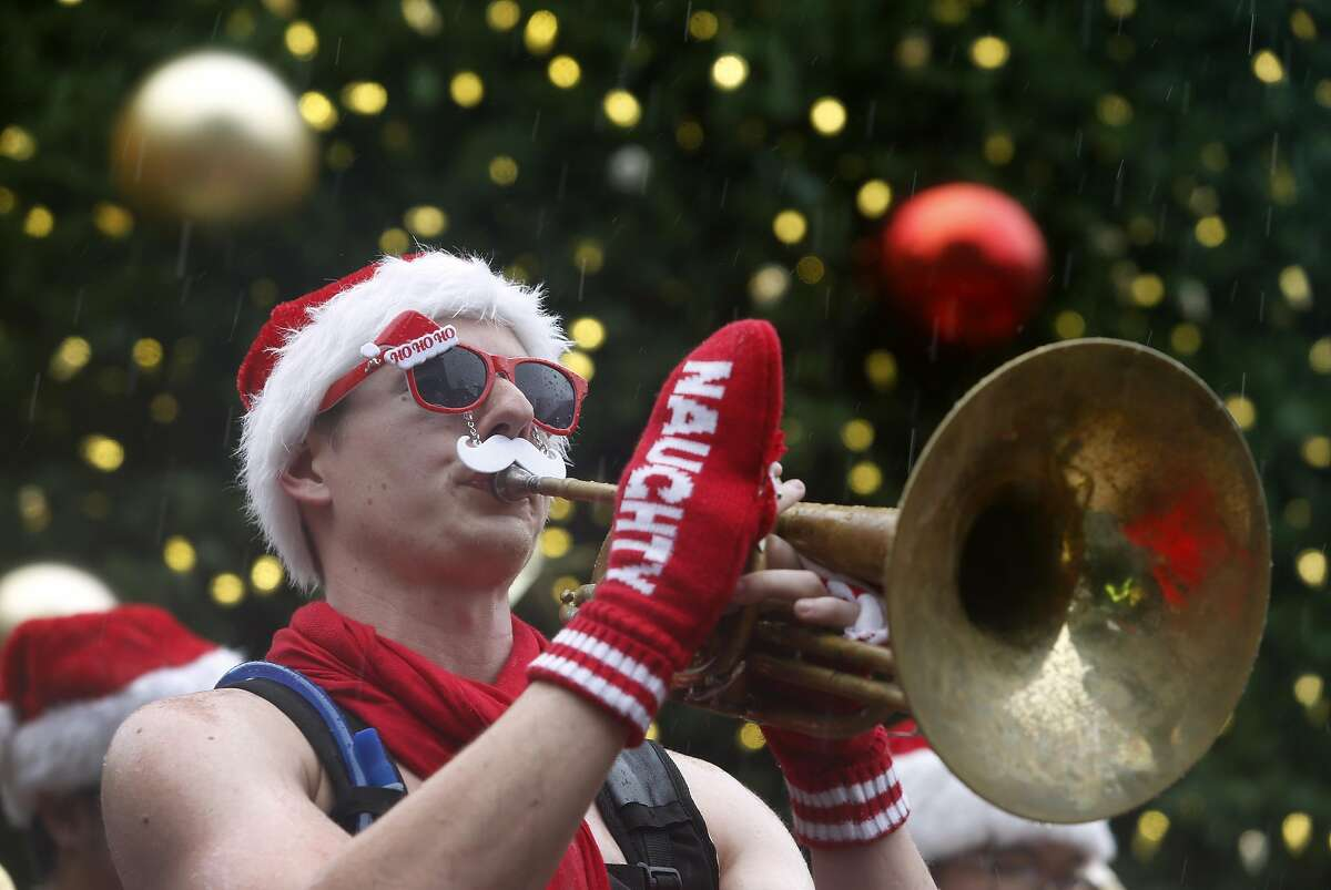 Joe Zimmerman and others in the Burlesque Band of San Francisco entertain multiple Santa Clauses at Union Square for the annual Santacon romp in San Francisco, Calif. on Saturday, Dec. 10, 2016.