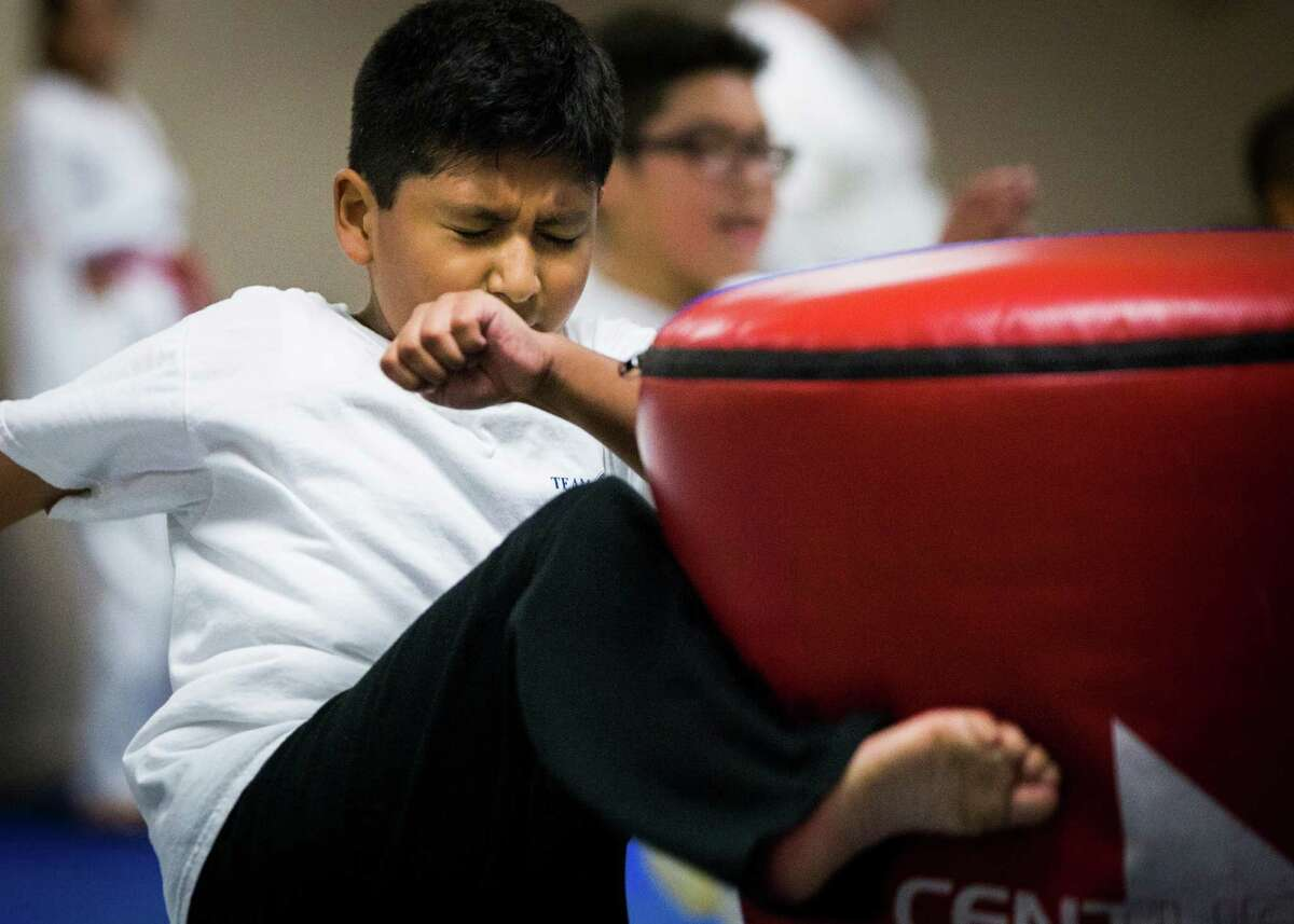 Carlos Gonzalez, 8, practices his kick during a taekwondo class. Gonzalez has defiant behaviors due to autism, but Aldine ISD at first refused to acknowledge he had a disability.