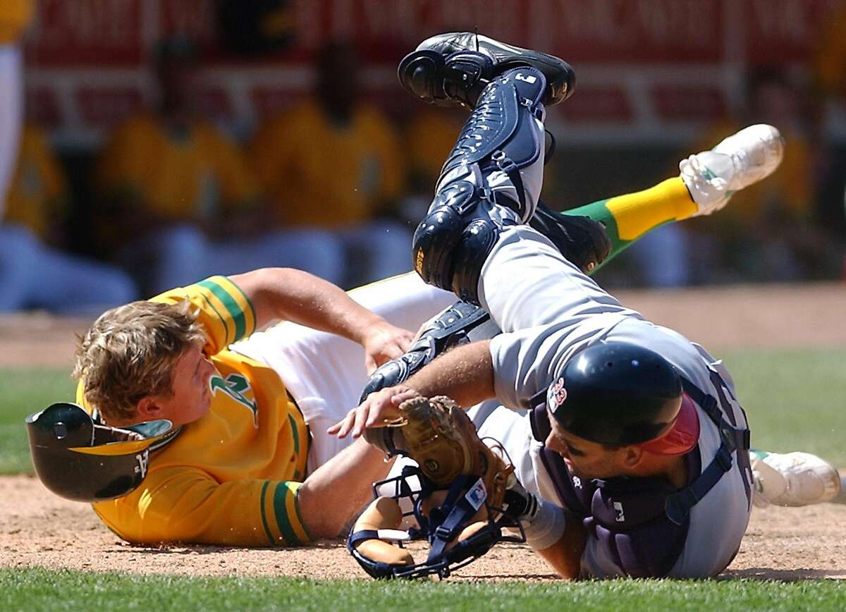 Oakland Athletics' Eric Byrnes, left, collides with Texas Rangers catcher Bill Haselman after being tagged out at home plate in the ninth inning Sunday, July 21, 2002, in Oakland, Calif. Byrnes was attempting to score from third on a fly ball by Mark Ellis. Texas won 7-3 in 12 innings. The Rangers wer wearing the uniforms of the 1961 Washington Senators, while the Athletics were wearing those of the 1972 world champion Athletics. (AP Photo/Ben Margot)