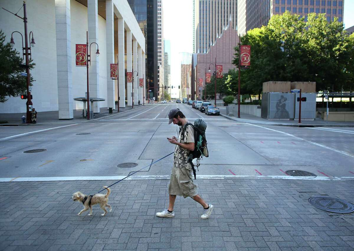 Patrick Gillespie and his dog Franklin walk through downtown Houston on their way inquire about getting a new ID for Gillespie, Wednesday, Nov. 16, 2016. Gillespie, 30, has spent years of his adult life homeless, traveling around the country, hitch-hiking, sleeping outside and working when he has the chance. In October, after being arrested for trespassing, Patrick was holding a sign asking for help getting his dog out of the local shelter. Wilma Price, who runs a local dog rescue, helped Patrick out that day and then started a GoFundMe. The GoFundMe has raised almost $20,000 to date. ( Mark Mulligan / Houston Chronicle )