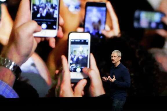 FILE - In this Wednesday, Sept. 7, 2016, file photo, Apple CEO Tim Cook announces the new iPhone 7 during an event to announce new products, in San Francisco. Apple reported Tuesday, Oct. 25, 2016, that it sold 45.5 million iPhones in the previous quarter, 5 percent fewer than it sold a year earlier. But the giant tech company's rosy forecast for the holidays was better than what Wall Street had been expecting. (AP Photo/Marcio Jose Sanchez, File)