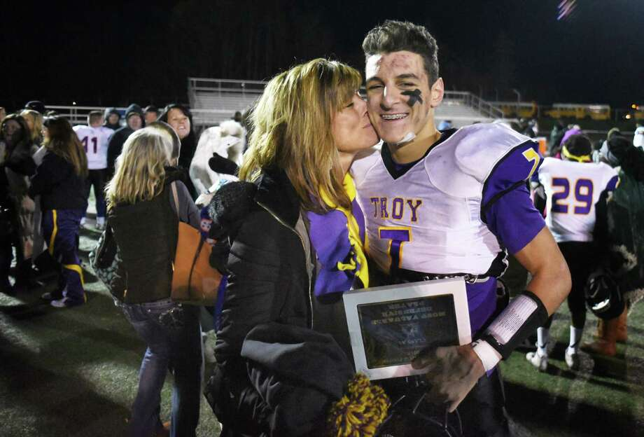 Defensive player of the game, Troy QB #7 Joe Casale gets a kiss from his mother Kathy Casale after Troy won their State Class AA quarterfinal against Newburgh Free Academy at Dietz Stadium in Kingston, NY.  (John Carl D'Annibale / Times Union) Photo: John Carl D'Annibale / 20038761A