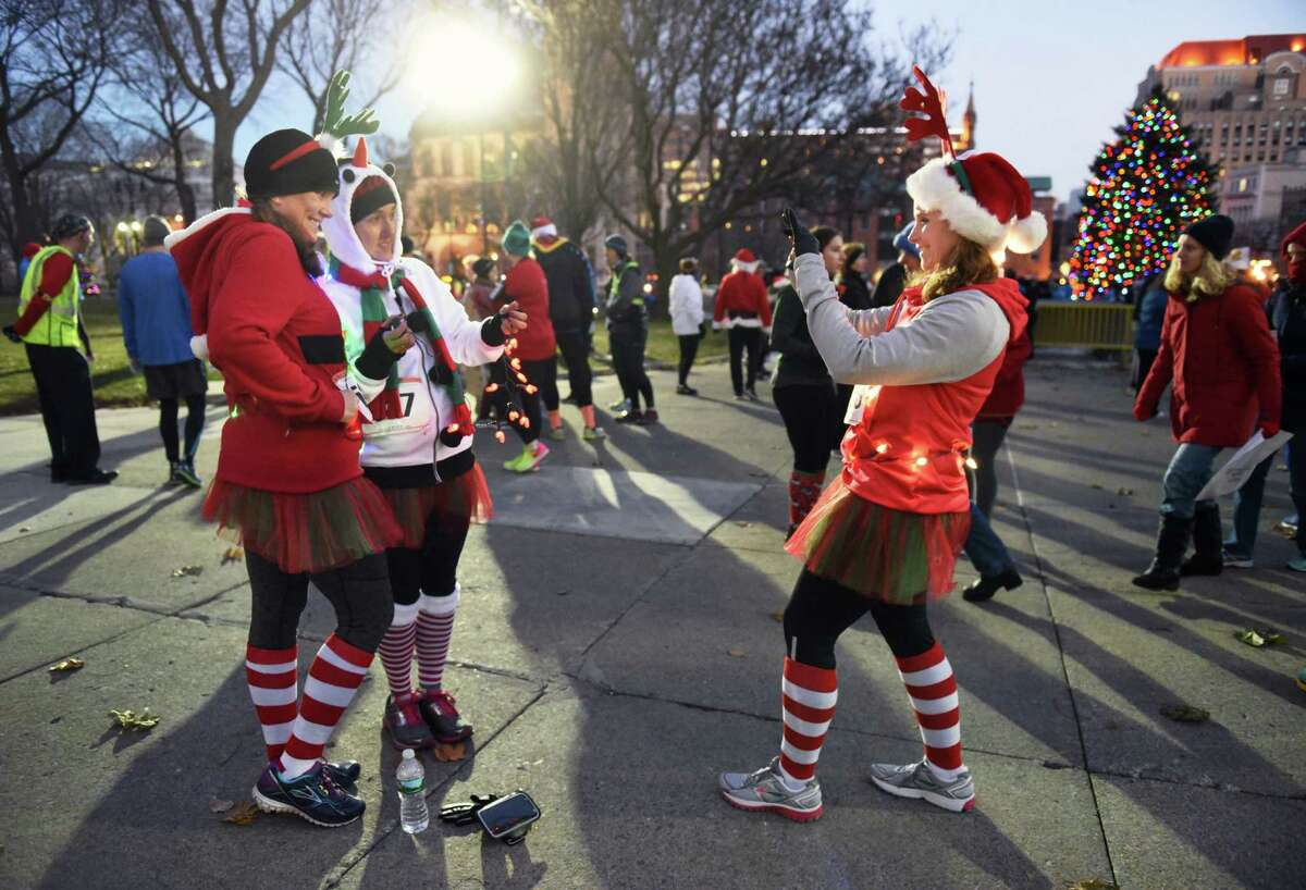 Lindsay Foley, left, of Albany and Erin Govel of Guilderland pose for a photo by their running partner Mary Ellen Myer, right, of Guilderland before the start of the 20th annual Albany Last Run 5K in front of Albany City Hall Saturday Dec. 10, 2016 in Albany, NY. (John Carl D'Annibale / Times Union)