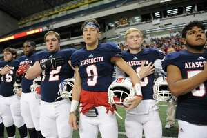 Randall Mccusker (9) and other Atascocita teammates stand at attention during the National Anthem before the Conference 6A Division I State Semi-Final playoff game between the Atascocita Eagles and the Lake Travis Cavaliers on Saturday December 10, 2016 at the Alamodome, San Antonio, TX.