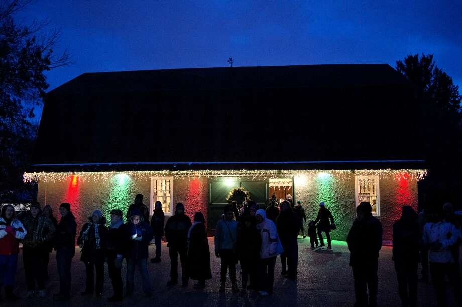 Guests gather outside the historic barn during the Christmas Walk on Saturday at Dow Gardens. One more walk is scheduled for Dec. 16-17, from 5-7:30 p.m. The event is free. Photo: NICK KING | Nking@mdn.net