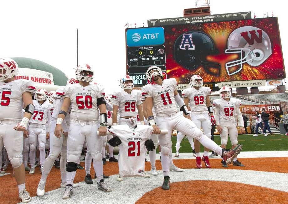 The Woodlands defensive linemen Conner Barnett (50) and linebacker Zach La Canfora (11) hold the jersey of linebacker Grant Milton (21) as the team prepares to take the field before a Class 6A Division I state semifinal game at Darrell K Royal-Texas Memorial Stadium Saturday, Dec. 10, 2016, in Austin. Milton suffered a serious head injury during the team's Nov. 26 win over Austin Bowie in a UIL Class 6A Division I regional semifinal playoff game at Baylor's McLane Stadium. He was taken to a Waco hospital to have emergency surgery where he remains in a medically induced coma. Photo: Jason Fochtman/Houston Chronicle