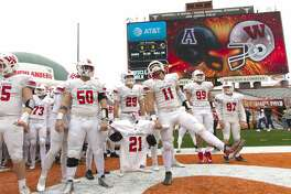 The Woodlands defensive linemen Conner Barnett (50) and linebacker Zach La Canfora (11) hold the jersey of linebacker Grant Milton (21) as the team prepares to take the field before a Class 6A Division I state semifinal game at Darrell K Royal-Texas Memorial Stadium Saturday, Dec. 10, 2016, in Austin. Milton suffered a serious head injury during the team's Nov. 26 win over Austin Bowie in a UIL Class 6A Division I regional semifinal playoff game at Baylor's McLane Stadium. He was taken to a Waco hospital to have emergency surgery where he remains in a medically induced coma.