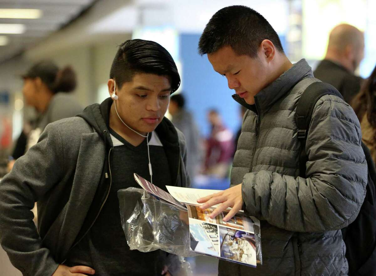 Liberty High School senior Antonio Lucas, left, and freshman Wei Lin look at through pamphlets for college information at Houston Independent School District's second DREAM Summit Saturday, Dec. 10, 2016, in Houston. Nonprofit organizations and college officials were on site to provide students with information about financial aid, student housing, applications and options.