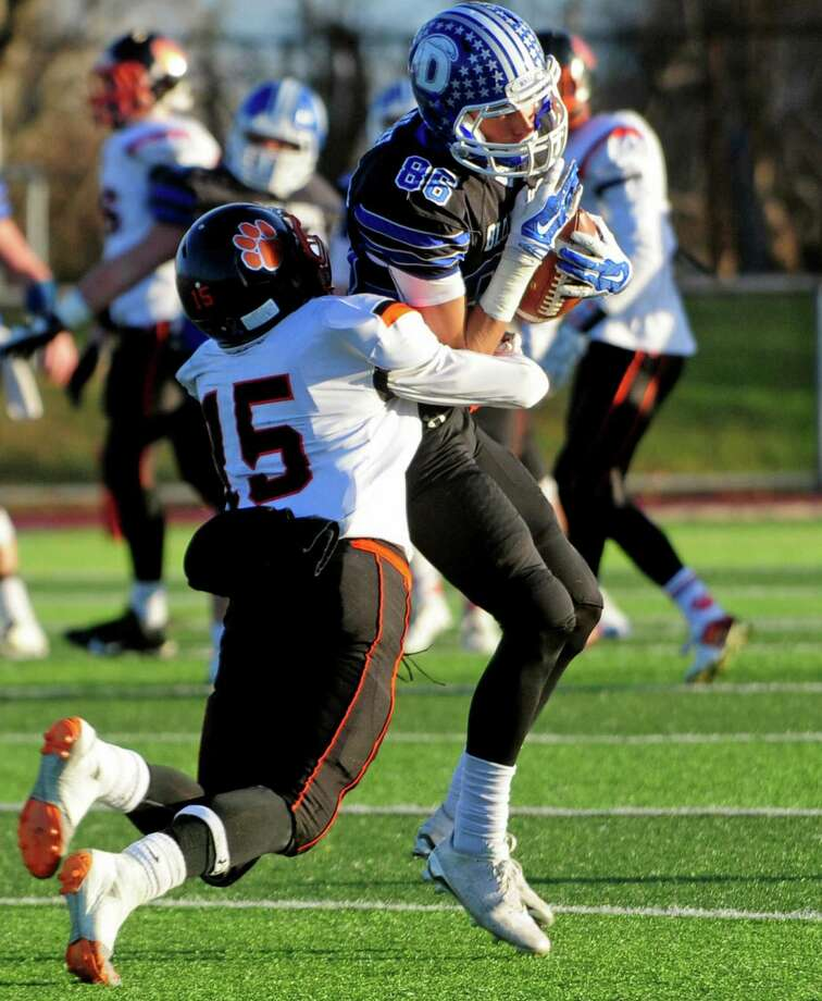 Darien's Spencer Jarecke completes a pass as he gets tackled by Ridgefield's Aidan Spearman during Class LL Championship football action in West Haven, Conn. on Saturday Dec. 10, 2016. Darien defeated Ridgefield 28-7. Photo: Christian Abraham / Hearst Connecticut Media / Connecticut Post