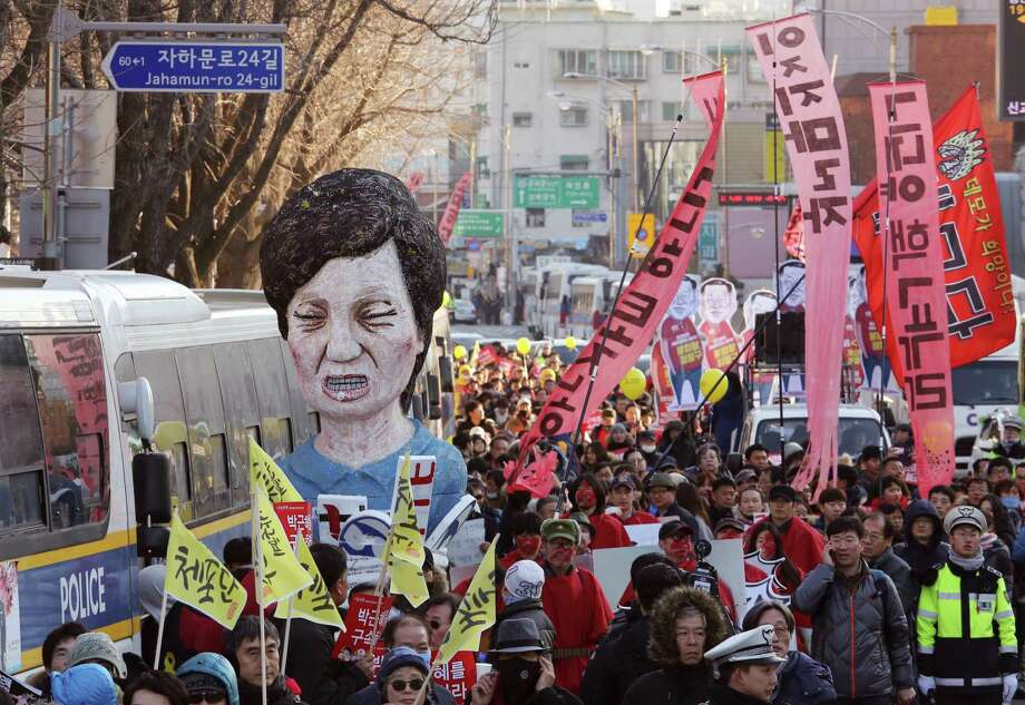 """Protesters carry an effigy of impeached South Korean President Park Geun-hye as they march toward the presidential house during a rally in Seoul Saturday, Dec. 10, 2016. Shifting from protests to celebration, large crowds of South Koreans were expected to march near the presidential house on Saturday to cheer the impeachment of disgraced president over an explosive corruption scandal. The sign read """"Impeach Park Geun-hye immediately."""" (AP Photo/Ahn Young-joon) ORG XMIT: SEL102 Photo: Ahn Young-joon / Copyright 2016 The Associated Press. All rights reserved."""