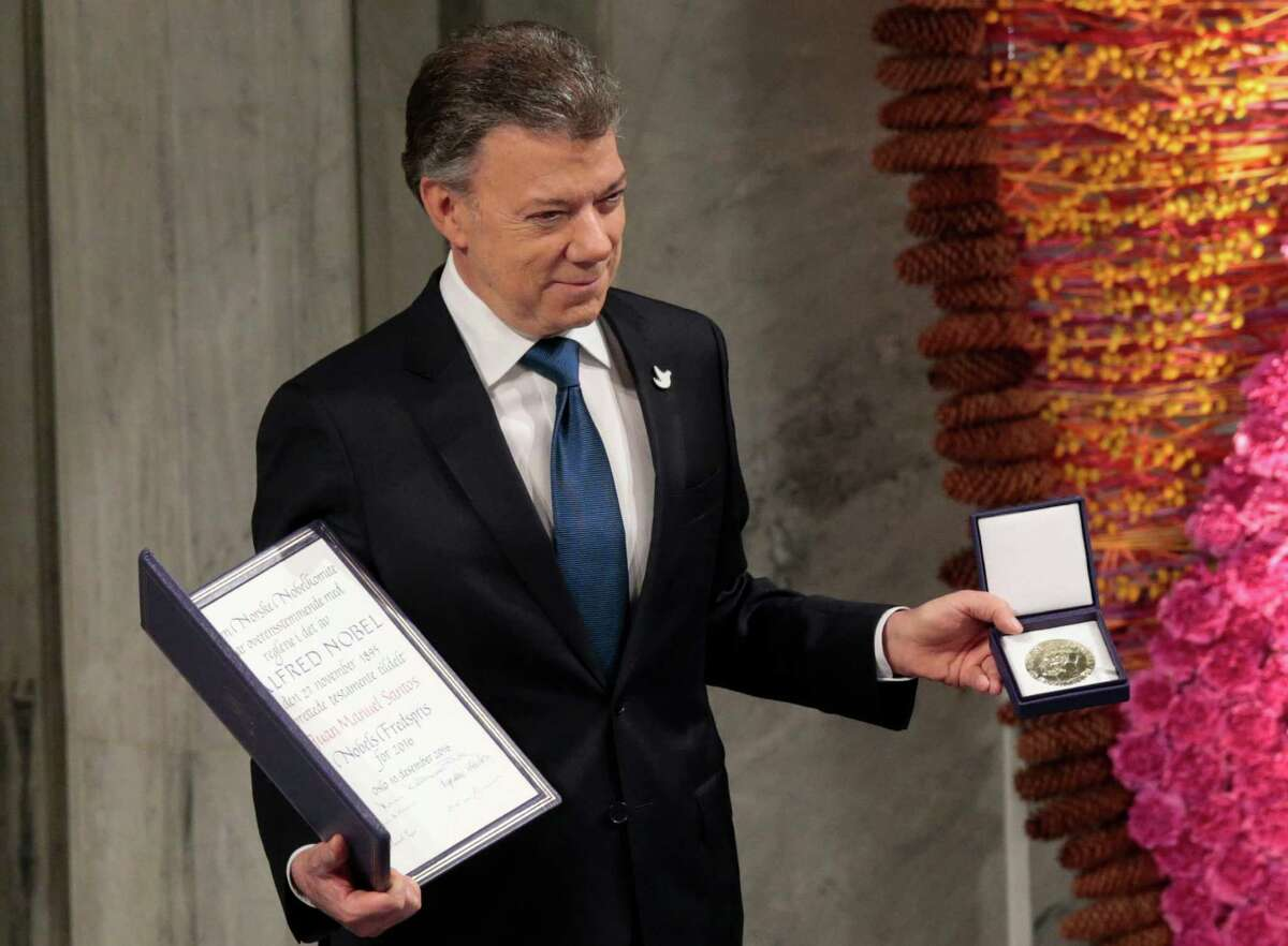 Nobel Peace Prize Laureate Colombian President Juan Manuel Santos pose with the medal and diploma during the Peace Prize awarding ceremony at the City Hall in Oslo, Saturday Dec. 10, 2016. President Juan Manuel Santos is awarded this year's Nobel Peace Prize for his efforts to bring Colombia's more than 50-year-long civil war to an end. (Lise Aaserud / NTB scanpix via AP)